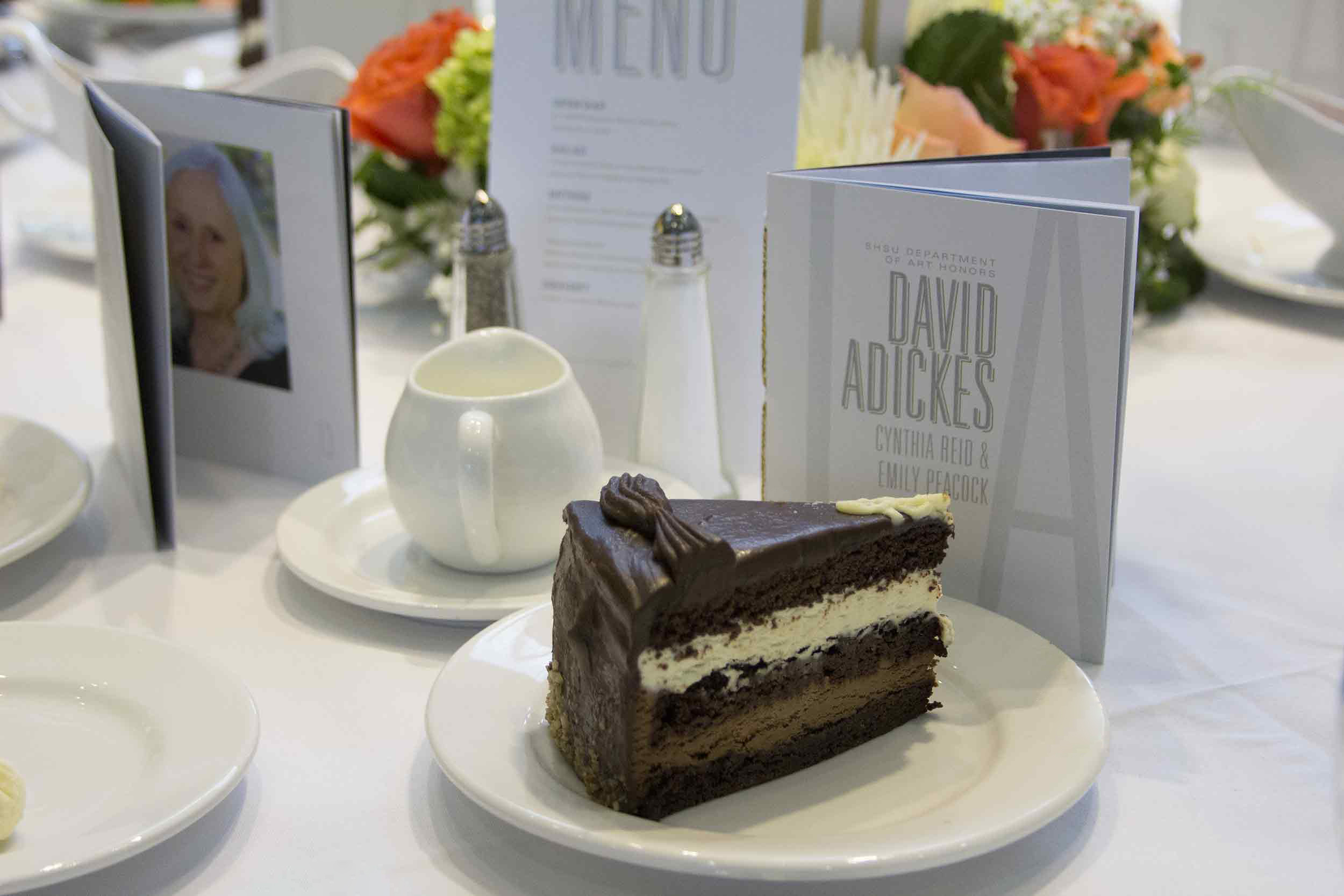 Triple layer choclate cake on a white plate with white linens with gala program and menu on a table adjacent to a vibrant floral arrangement